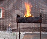 A lenha e o fogo no carvão vegetal oxidado velho grelham fotografia de stock
