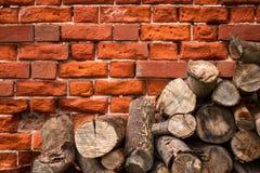 Lenha em um fundo da parede de tijolo Fotos de Stock