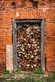 A lenha encontra-se na entrada, parede de tijolo vermelho Imagem de Stock