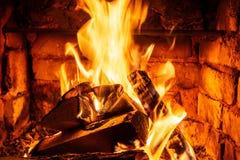 Lenha que queima-se em queimaduras do fogo na chaminé O forno do tijolo dá o calor e o calor dos logs queimados Carvões e chamas  imagem de stock royalty free