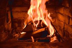 Lenha que queima-se em queimaduras do fogo na chaminé O forno do tijolo dá o calor e o calor dos logs queimados Carvões e chamas  imagens de stock