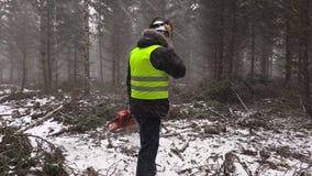 Lenhador com serra de cadeia que fala no telefone celular na tempestade das nevadas fortes vídeos de arquivo