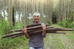 Lenhador fêmea que leva uma pilha de troncos Imagem de Stock Royalty Free