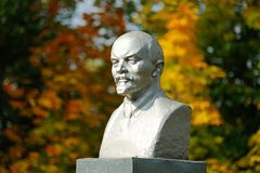 Lenin bust monument with autunm leaves on the background. Horizontal Stock Photo