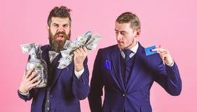 Lening en bankwezenconcept Mensen in kostuum, zakenlieden met kruikhoogtepunt van contant geld en creditcard, roze achtergrond Ri royalty-vrije stock foto's