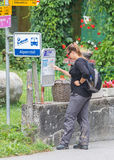 LENK, SWITZERLAND - JULY 23, 2015: Young woman checking the time. Table at the bus stop in Lenk, Switzerland on July 23, 2015 Stock Image