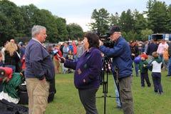 Lenken Sie den interviewenden Mann mit 6 Nachrichten am Ballon-Festival, Crandall-Park, Glens Falls, New York, 2014 Lizenzfreies Stockfoto