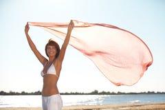 Lenço feliz da terra arrendada da mulher nova na praia Fotografia de Stock Royalty Free