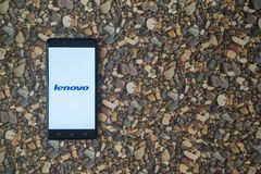 Lenovo-Logo auf Smartphone auf Hintergrund von kleinen Steinen Lizenzfreies Stockbild