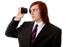 Lens. Young man looking through a lens stock image