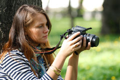 Lens. The girl-photographer in spring park Royalty Free Stock Photos