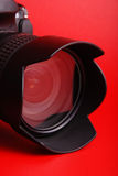 Lens. SLR camera lens on red background Royalty Free Stock Photography