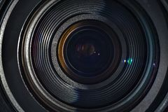 The lens of a camera. The front lens of the camera lens. Colorful reflections is not glass. Enlightenment lenses of camera lenses. Black frame and glass Stock Photo