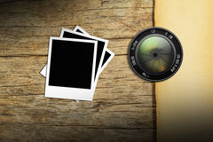 Lens  camera  with   photo frame on wood background Stock Images