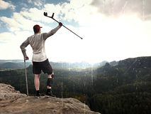 Hiker huts knee. Man with leg in join immobilizer stay on summit and raise medicine cruth above head. Hiker achieved peak. Lens defect. Hiker huts knee. Man with Royalty Free Stock Photos