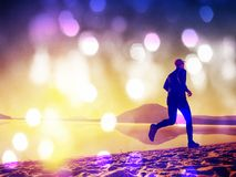 Tall fit man running along the sea shore in morning. Healthy male jogging on lake beach. Lens defect. Tall fit man running along the sea shore in morning Stock Photos