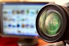 Lens of dslr camera and monitor. Lens of dslr camera and computer monitor with blurred photos on  background Royalty Free Stock Image
