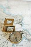 Lens en kompas op een kaart! Stock Afbeelding