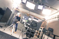 Film camera in broadcasting studio, spotlights and equipment, cameraman in the blurry background. Lens of a film camera in an television broadcasting studio royalty free stock photos