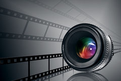 Lens & film strip on black. Lens and film strip on black background Stock Images