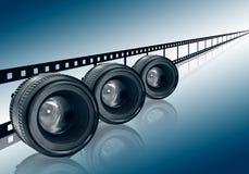 Lens & film strip on blue background Royalty Free Stock Photos
