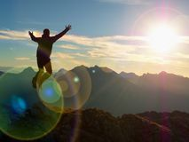 Lens flare effect. Bow light circles. Crazy hiker jumping at peak of mountain. Tourist jump on rock above  foggy valley. Mountains increased from humidity Royalty Free Stock Images