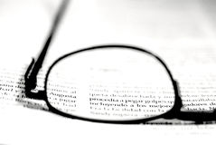 Lens of glasses over text. Lens of glasses or spectacles over black text with white background, clear ideas business concept Royalty Free Stock Photography
