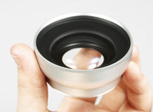 Lens in a hand Royalty Free Stock Photography