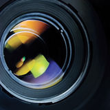 Lens and hood, large detailed macro zoom closeup, black, blue, green, red reflections in glass Stock Photos