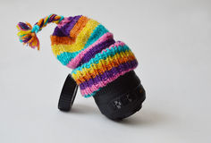 Lens with a knitted hat on and a lens cap Stock Photos