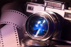 Lens with an old retro film camera. Background camera and negative film Royalty Free Stock Photo