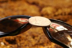 The lens part of sunglasses. The lens part of sunglasses with money coin represent the protective eyewear business concept related idea Royalty Free Stock Photo