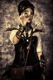 The lens. Portrait of a beautiful steampunk woman over grunge background Stock Photos