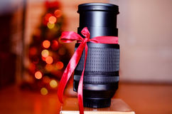 Lens with red ribbon for present Royalty Free Stock Images