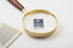 Lens and Stamps. Collecting Stamps, verify them with a lens Royalty Free Stock Photo