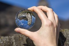 Lensball and Gothic church in Ludrova, Slovakia. Crystal lensball in hand and ancient gothic church of All Saints Ludrova, Slovakia stock photos