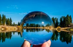 A Brilliant Blue Sky And A Lensball. A lensball produces an image of a bright sunny blue sky and the reflective beauty of local pond stock image