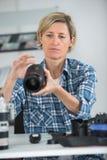 Lense profissional da câmera da limpeza da mulher foto de stock royalty free