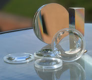 Lenses, mirrors and prisms. An assortment of various lenses, mirrors, and prisms stock photo