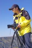 Lensman e la sua macchina fotografica immagine stock