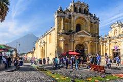 Lent carpets outside church & volcano, Antigua, Guatemala. Antigua, Guatemala - April 2, 2017: Pine needle procession carpets outside Hermano Pedro church during stock images