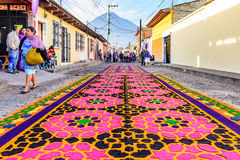 Lent carpets & volcano, Antigua, Guatemala. Antigua, Guatemala - April 2, 2017: Dyed sawdust procession carpets during Lent against backdrop of Agua volcano in royalty free stock photography