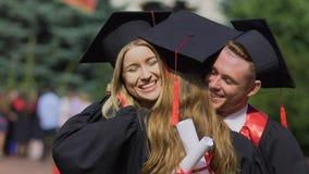 Lent-MOIS des diplômés heureux échangeant des félicitations, amis étreignant chaudement banque de vidéos