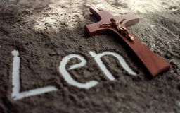 Lent word written in ash and christian cross as a T letter a religion concept Ash wednesday. Background stock photos