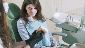 Lentamente sparare al paziente sta sedendosi nell'ospedale nell'ufficio del ` s di medico nella sedia dentaria, il dentista gli d stock footage