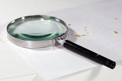 Lente che si trova sul foglio di carta bianco immagine stock