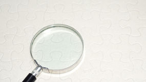 Lente con il puzzle vuoto Foto di concetto Fotografie Stock
