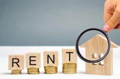 Lente d'ingrandimento, blocchi di legno con l'affitto di parola, monete e una casa miniatura Il concetto di affitto alloggio e de immagini stock