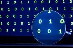 Lente d'ingrandimento che cerca il codice dai dati binari fotografie stock