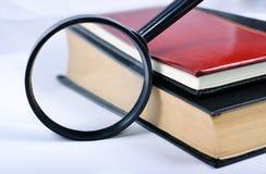 Lente d'ingrandimento con i libri Immagini Stock